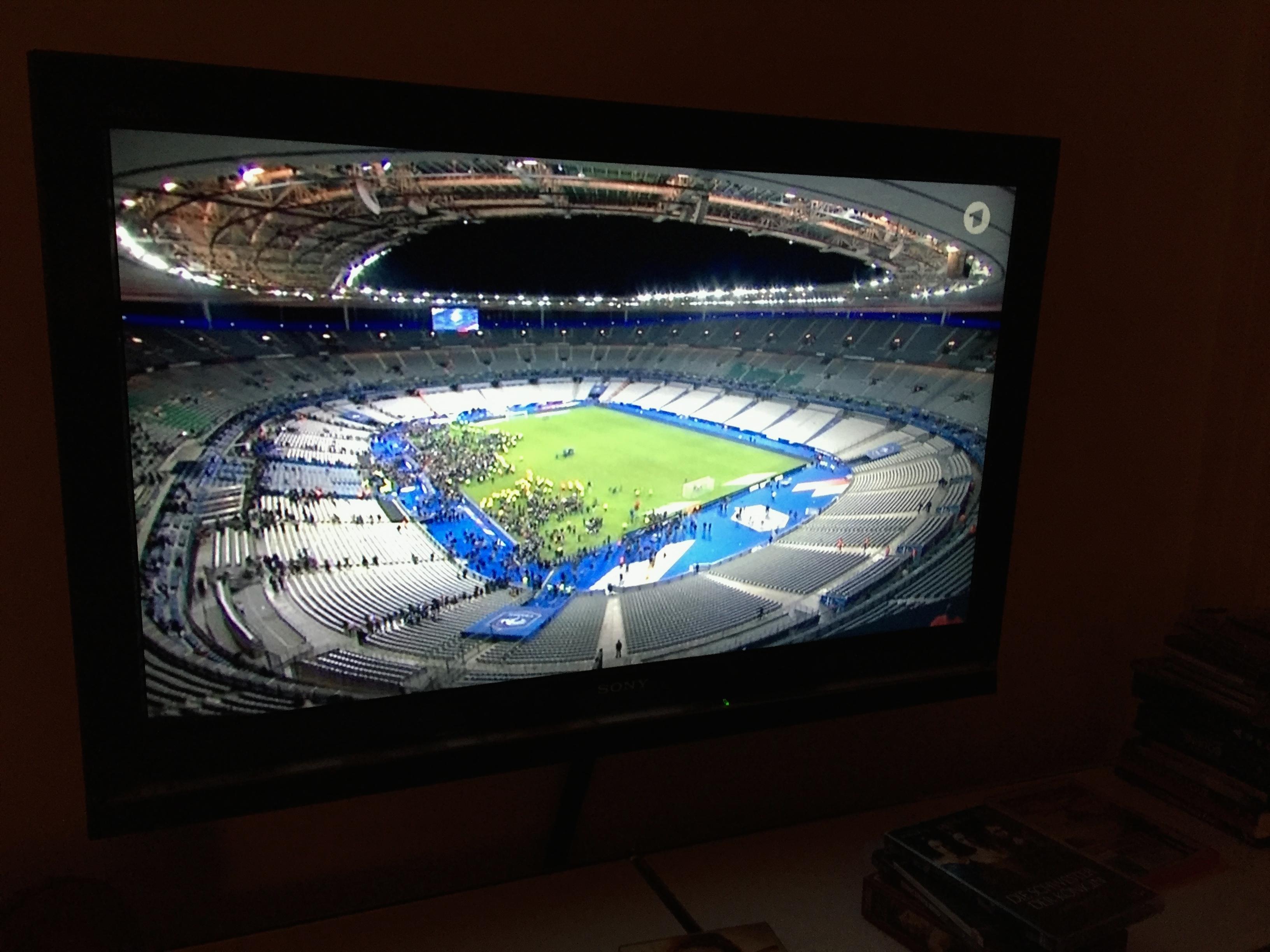 Unser Fernseher mit dem Bild vom Stade de France, auf dem zu sehen ist, wie die Ordner das Publikum von der Innenfläche zu den geöffneten Toren leitet. ©Maja Peltzer